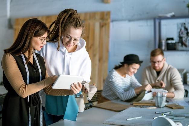 Due femmine creative piuttosto giovani che parlano di nuovi modelli di moda o tendenze sul display del touchpad nell'ambiente di lavoro