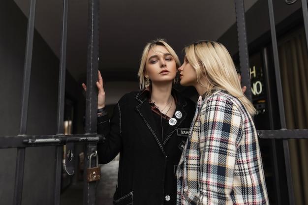 Due ragazze bionde piuttosto giovani in abiti eleganti con labbra sexy in posa vicino al cancello di ferro all'aperto iron