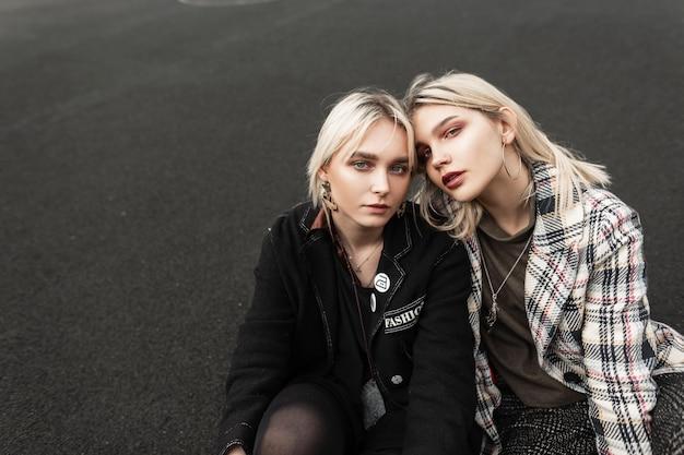Due ragazze bionde piuttosto giovani in abiti eleganti con labbra sexy si rilassano sull'asfalto all'aperto