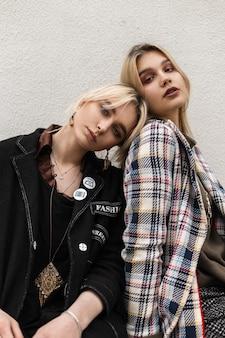 Due ragazze bionde piuttosto giovani in abiti eleganti con labbra sexy si rilassano su un tubo d'argento vicino al muro all'aperto