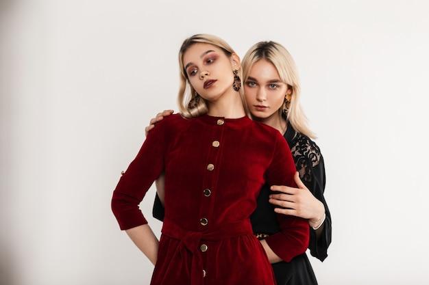 Due ragazze bionde piuttosto giovani in abiti eleganti con labbra sexy in posa vicino al muro bianco vintage al chiuso