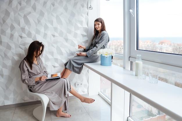 Due belle sorelle gemelle che fanno colazione e leggono un libro vicino alla finestra