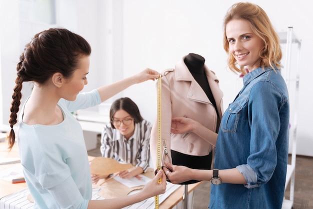 Due graziosi giovani sarti che prendono le misure della manica di una giacca rosa appesa al manichino mentre il loro collega è impegnato con i modelli di vestiti