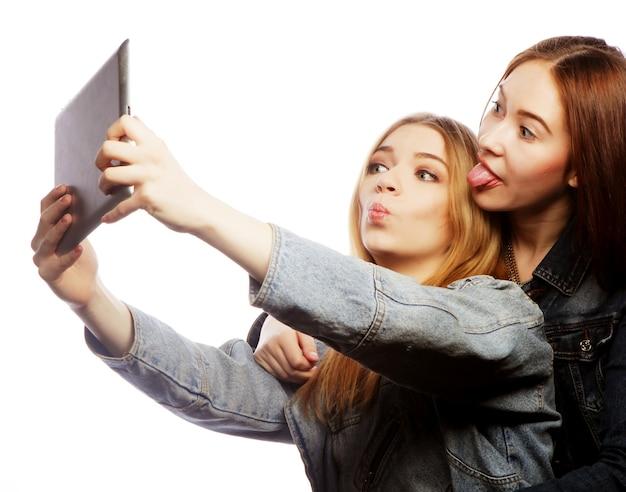 Due belle giovani donne che prendono un autoritratto con un tablet, isolato su bianco