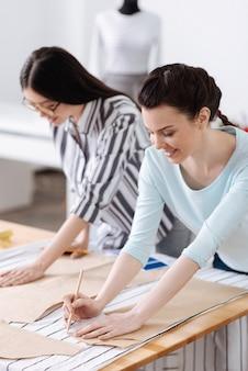 Due belle giovani donne che tracciano motivi sui tessuti, usando le matite per questo e sembrano totalmente coinvolte nel processo