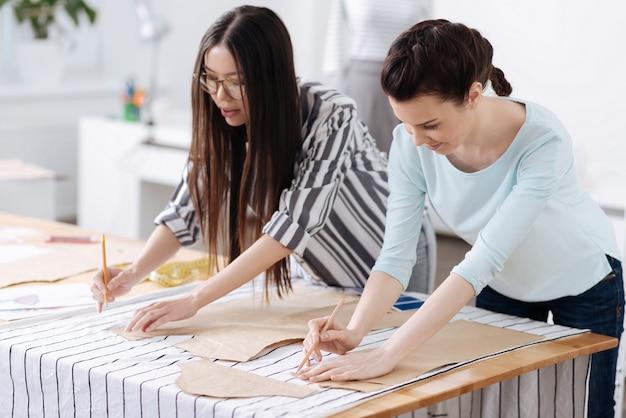 Due belle giovani donne che tracciano modelli su tessuti a righe, sembrano completamente impegnate nel processo.
