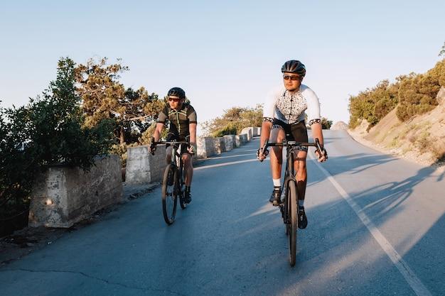 Due ciclisti maschi professionisti che guidano insieme le loro biciclette da corsa al mattino