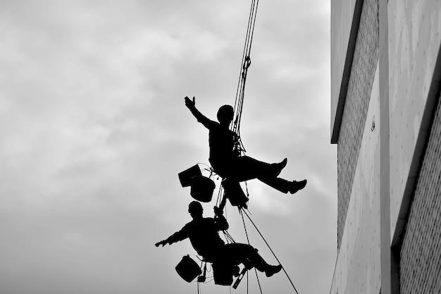 Due professionisti isolano un edificio residenziale all'esterno. alpinismo industriale. due scalatori isolano il muro della casa sulle corde.