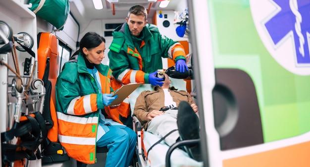 Due paramedici professionisti in un'ambulanza con un paziente in barella