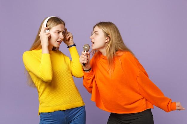 Due sorelle gemelle bionde perplesse in abiti colorati ascoltano musica con le cuffie cantano una canzone nel microfono isolato sulla parete blu viola. concetto di stile di vita familiare di persone.