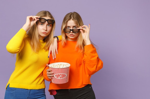 Due giovani sorelle gemelle bionde perplesse in occhiali 3d imax che guardano film in possesso di popcorn isolato su parete blu viola pastello. concetto di stile di vita familiare di persone.