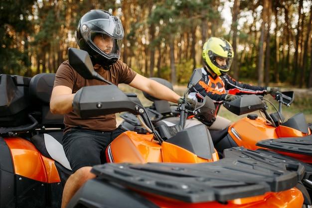 Due motociclisti quad in caschi e attrezzature, vista laterale, primo piano, foresta estiva sullo sfondo. piloti maschi di quad, guida atv, sport estremi