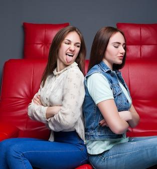 Due ragazze litiganti si siede sul divano in pelle rossa. fine dell'amicizia femminile. le donne litigano