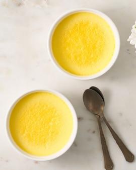 Due ramekin con le uova di appoggio della frittata nella frittata fresca della ciotola con la vista superiore del cucchiaio