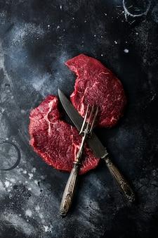 Due bistecche di manzo crude con spezie, cipolle e peperoncino su ardesia scura o sfondo di cemento. vista dall'alto