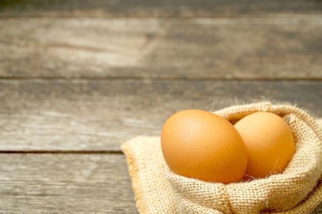 Due uova di pollo crudo in sacco di iuta (sackcloth) su sfondo di legno. marrone biologico.
