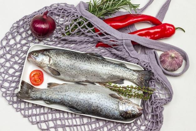 Trota di pesce crudo due sulla zolla bianca. pepe rosso e rametti di rosmarino sul sacchetto a rete. lay piatto.