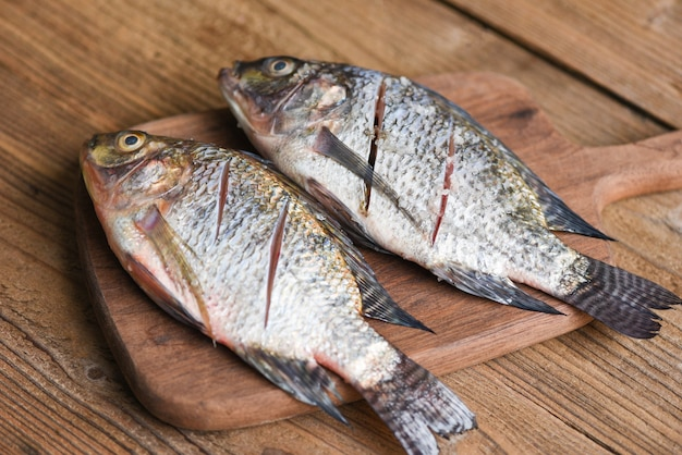 Due pesci d'acqua dolce di tilapia del nilo crudi sul bordo di legno di legno / pesce fresco di tilapia per cucinare il cibo