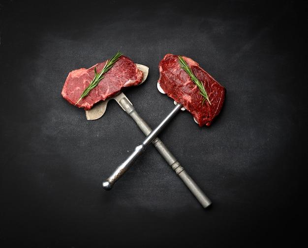 Due pezzi crudi di bistecca di manzo giacciono su un coltello di ferro, superficie nera. bistecca classica, vista dall'alto