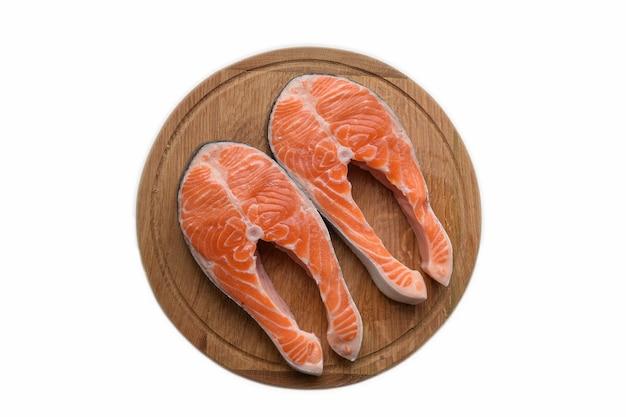 Due bistecche di pesce rosso crudo si trovano su una tavola rotonda di legno marrone di taglio. su sfondo bianco di ritaglio