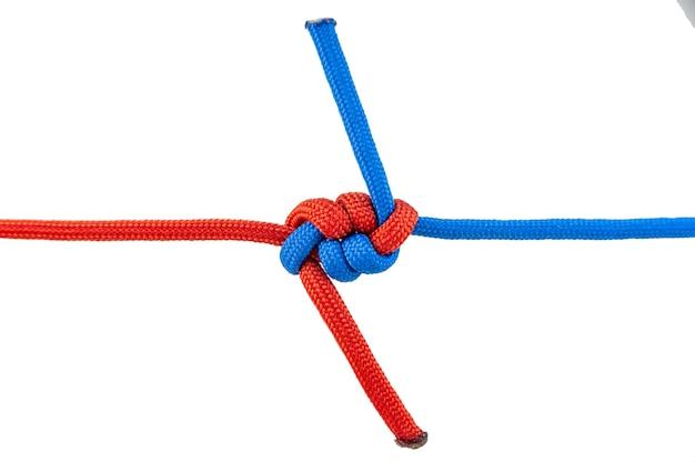 Sono collegati due cavi rosso e blu. nodo su un cavo isolato su uno sfondo bianco.