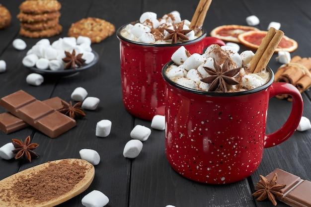 Due tazze rosse di cioccolata calda con marshmallow, anice e cannella cosparse di cacao in polvere