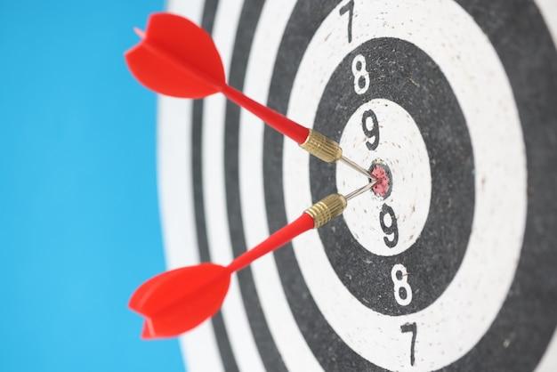 Due dardi rossi che colpiscono il primo piano dell'obiettivo del dardo su fondo blu