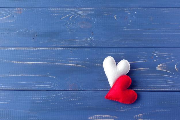 Due cuori di feltro rosso su sfondo bianco. simbolo di san valentino, concetto di vacanza. vista dall'alto con copia spazio per il testo.