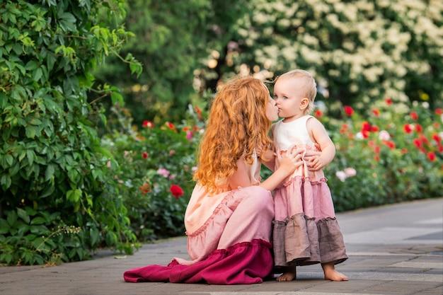 Due sorelle dai capelli rossi in lunghi abiti di lino riposano sul lago nel parco in una soleggiata giornata estiva. la ragazza più grande abbraccia e bacia il bambino.
