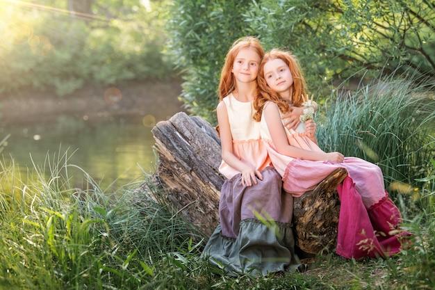 Due sorelle dai capelli rossi in lunghi abiti di lino riposano sul lago nel parco in una soleggiata giornata estiva.