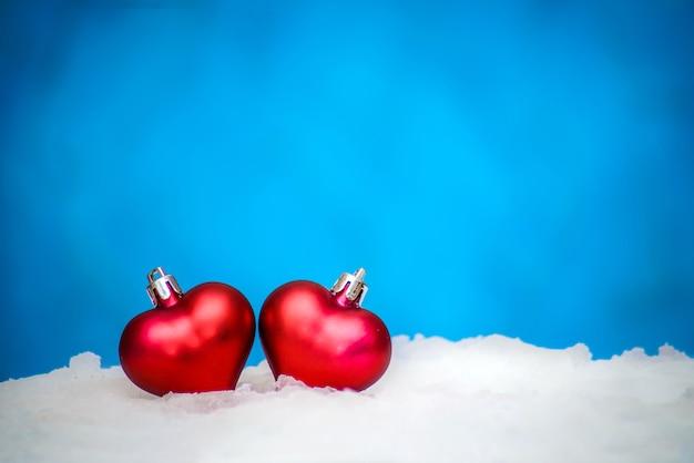 Due cuori rossi, giocattoli di natale nella neve su sfondo blu