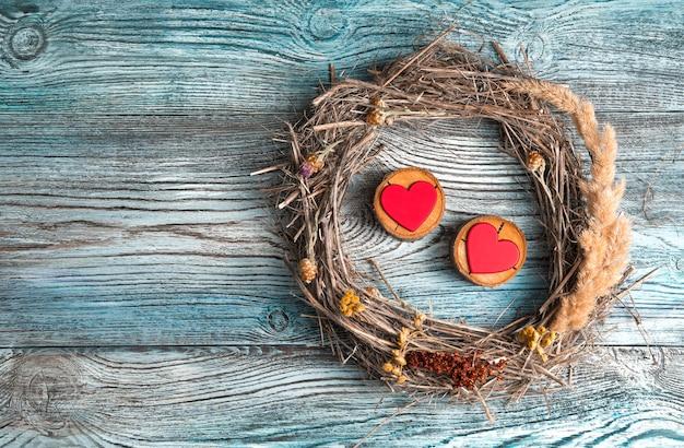 Due cuori rossi su un supporto di legno all'interno di una cornice di rami secchi ed erba su uno sfondo di legno.