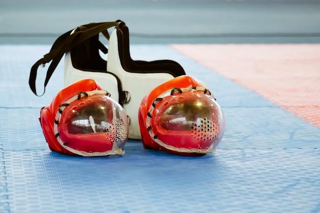Due caschi da combattimento di karate rossi con maschere di plastica trasparente e due giubbotti protettivi per il corpo sul pavimento