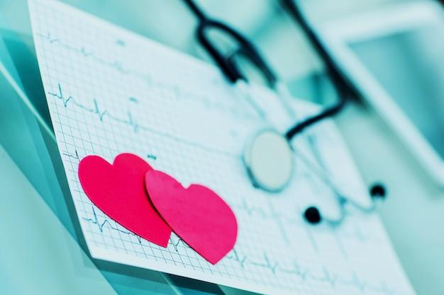 Due cuore di carta rossa sull'elettrocardiogramma il cardiologo
