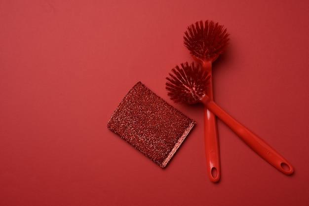 Due spazzole di plastica rosse e una spugna per lavare i piatti su fondo rosso, vista dall'alto