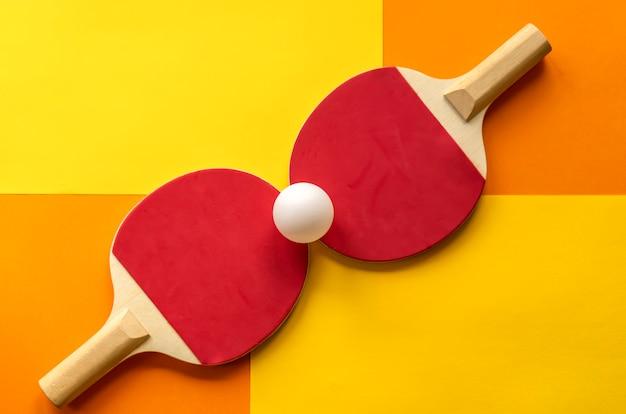 Due racchette da ping pong rosse giacciono su un colorato tavolo da ping pong