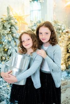 Due sorelle dai capelli rossi vicino all'albero di natale di capodanno