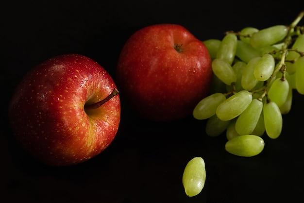 Due mele rosse fresche mature con gocce d'acqua sulla buccia lucida e grappolo d'uva verde sulla superficie nera