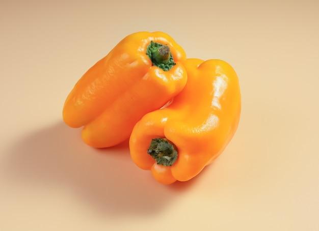 Due peperoni dolci gialli maturi abbinati su sfondo color mais