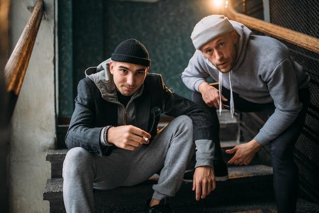 Due ladri in attesa di vittima sulle scale e fumatori. banditi di strada, criminali. pericolo di attacco di rapina