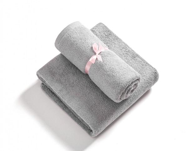 Due asciugamani di spugna arrotolati e piegati legati dal nastro rosa isolato. pila di asciugamani di spugna grigi contro uno sfondo bianco.