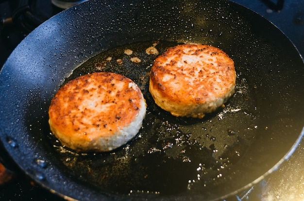 Due cotolette rotonde di carne di manzo vengono fritte in una padella e olio.