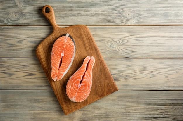 Due bistecche di salmone su un tagliere. composizione con bistecche di salmone sullo sfondo di un tavolo in legno con copia spazio.