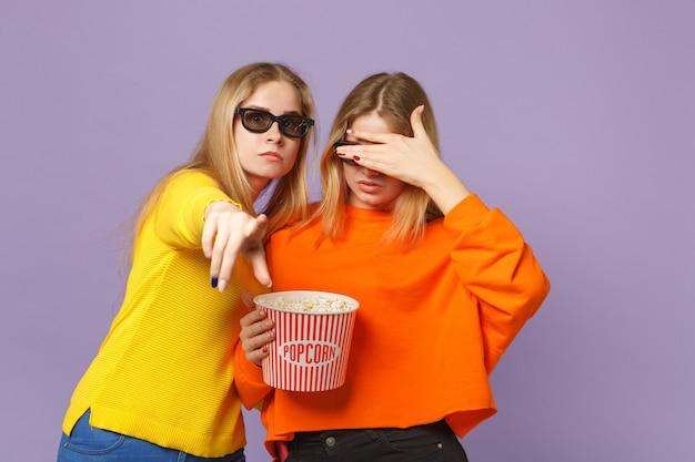 Due giovani sorelle gemelle bionde spaventate in occhiali 3d imax che guardano film in possesso di popcorn isolato su parete blu viola pastello. concetto di stile di vita familiare di persone.