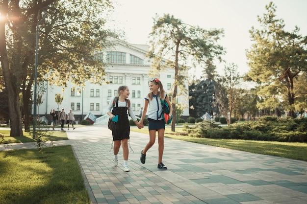 Due compagni di scuola camminano dopo le lezioni in un parco vicino alla scuola
