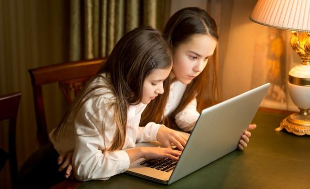 Due studentesse che fanno i compiti al laptop di notte