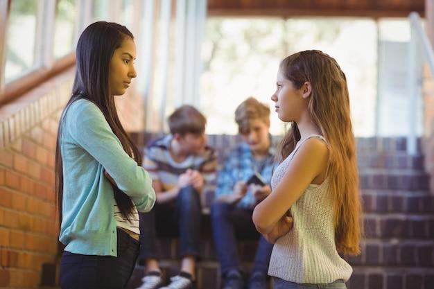 Due studentesse con le braccia incrociate in piedi faccia a faccia in corridoio