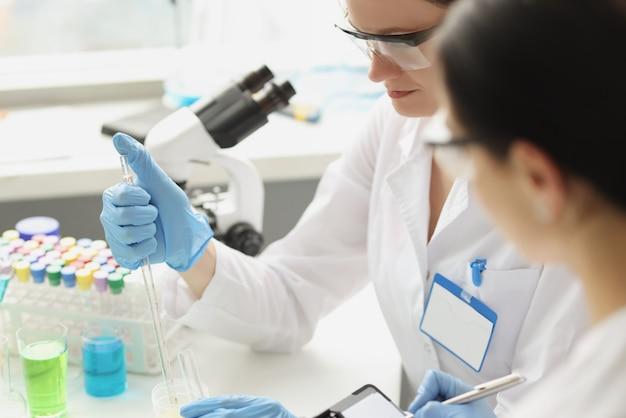 Due scienziati che conducono ricerche nello studio di laboratorio chimico sul concetto di composti chimici
