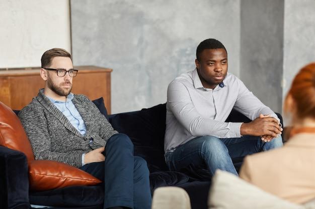 Due uomini seri e pensosi seduti sul divano e concentrati sulla soluzione dei loro problemi durante la terapia psicologica