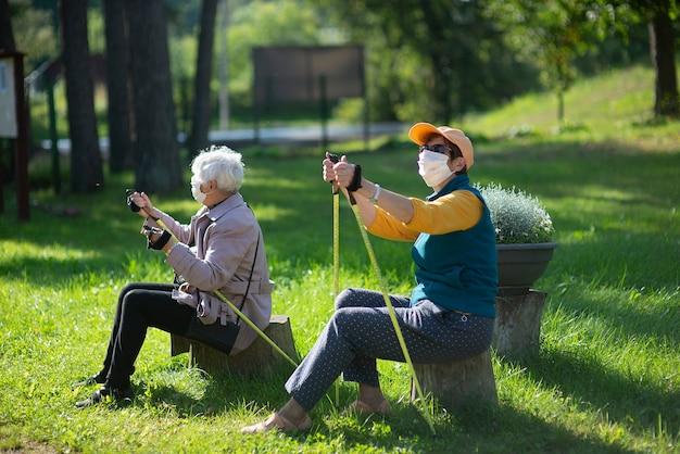 Due donne anziane anziane con maschere facciali riposano dopo una camminata nordica durante la pandemia covid-19